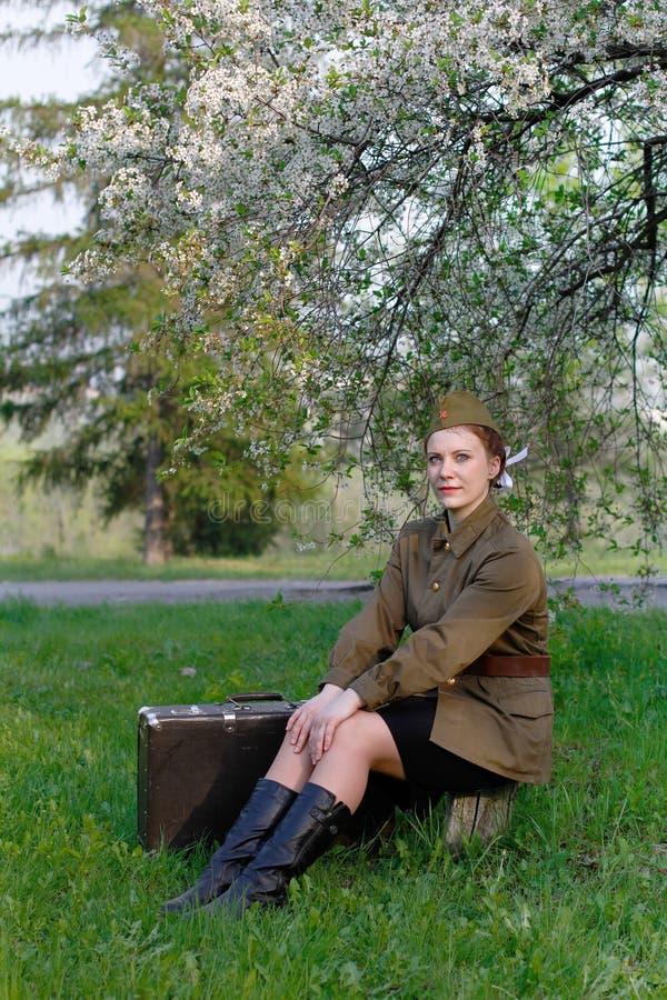 Ο σοβιετικός θηλυκός στρατιώτης σε ομοιόμορφο του Δεύτερου Παγκόσμιου Πολέμου με τη βαλίτσα κάθεται σε ένα κολόβωμα που ανθίζει π στοκ εικόνες
