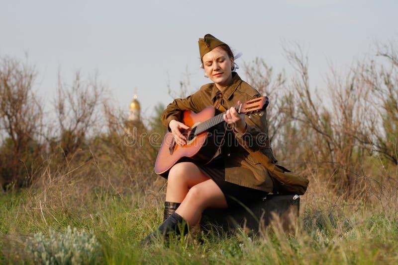 Ο σοβιετικός θηλυκός στρατιώτης σε ομοιόμορφο του Δεύτερου Παγκόσμιου Πολέμου παίζει την κιθάρα στοκ εικόνες με δικαίωμα ελεύθερης χρήσης
