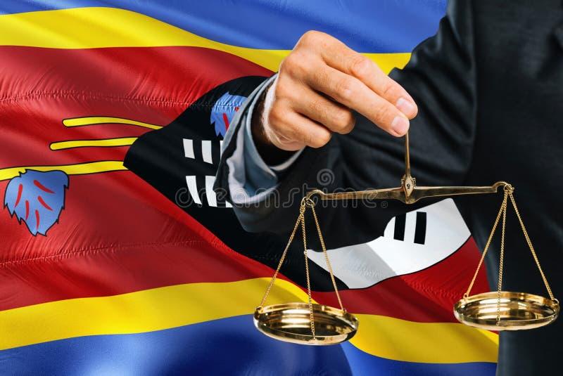 Ο σουαζηλανδικός δικαστής κρατά τις χρυσές κλίμακες της δικαιοσύνης με τη Σουαζιλάνδη που κυματίζει το υπόβαθρο σημαιών Θέμα ισότ στοκ φωτογραφίες
