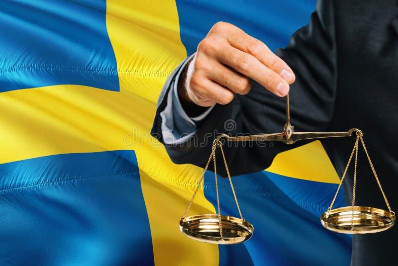 Ο σουηδικός δικαστής κρατά τις χρυσές κλίμακες της δικαιοσύνης με το κυματίζοντας υπόβαθρο σημαιών της Σουηδίας Θέμα ισότητας και στοκ φωτογραφία με δικαίωμα ελεύθερης χρήσης