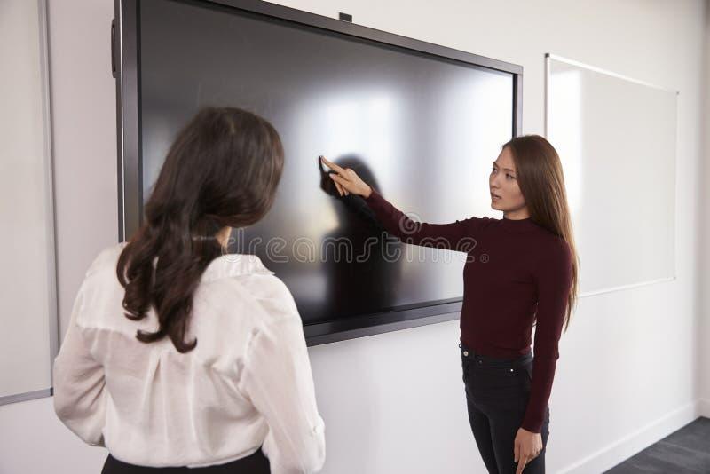 Ο σπουδαστής και ο δάσκαλος συζητούν το πρόγραμμα για διαλογικό Whiteboard στοκ εικόνα
