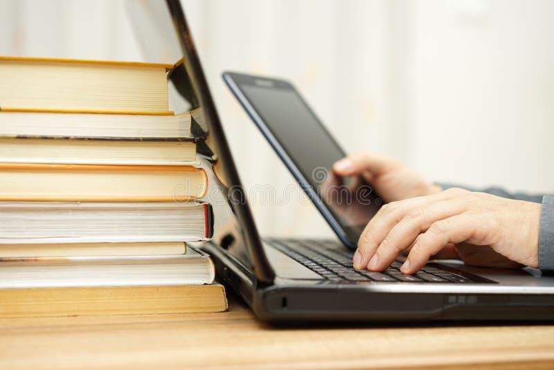 Ο σπουδαστής χρησιμοποιεί το PC ταμπλετών, το φορητό προσωπικό υπολογιστή και το διδακτικό υλικό στο τ στοκ εικόνα με δικαίωμα ελεύθερης χρήσης