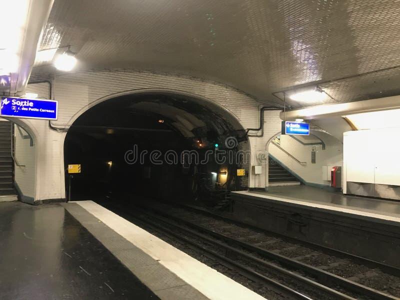 Ο σταθμός μετρό του Παρισιού με μια γκρίζα ποδιά και μια μαύρη σήραγγα, η πορεία πηγαίνει στην απόσταση, που διακοσμείται με τα ά στοκ εικόνες