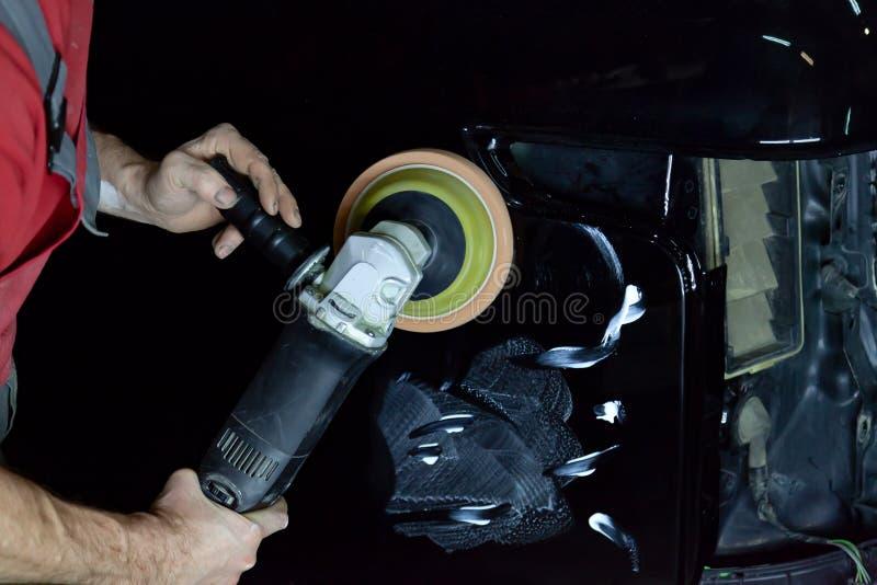 Ο στιλβωτής γυαλίζει το σώμα του οχήματος με το ειδικό κερί για να προστατεύσει το αυτοκίνητο από τις δευτερεύουσες αρχές και τη  στοκ φωτογραφία με δικαίωμα ελεύθερης χρήσης