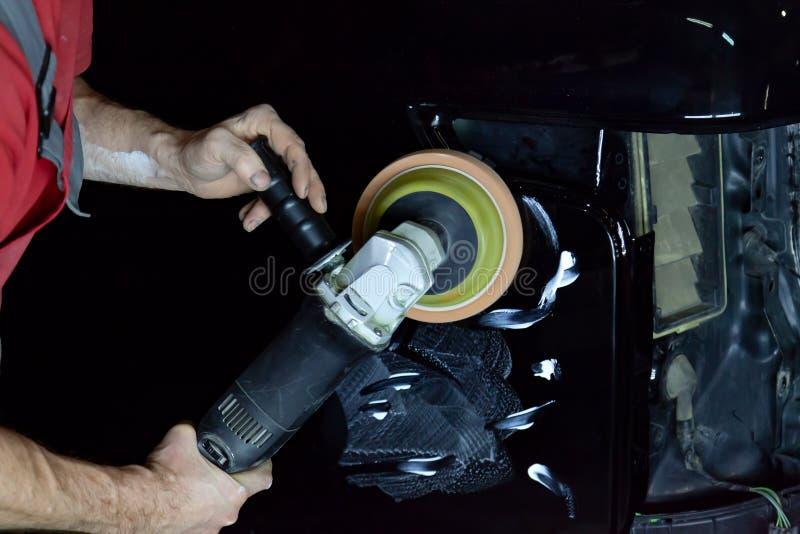 Ο στιλβωτής γυαλίζει το σώμα του οχήματος με το ειδικό κερί για να προστατεύσει το αυτοκίνητο από τις δευτερεύουσες αρχές και τη  στοκ φωτογραφίες με δικαίωμα ελεύθερης χρήσης