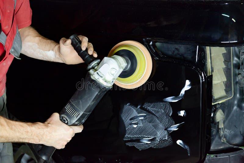 Ο στιλβωτής γυαλίζει το σώμα του οχήματος με το ειδικό κερί για να προστατεύσει το αυτοκίνητο από τις δευτερεύουσες αρχές και τη  στοκ φωτογραφίες