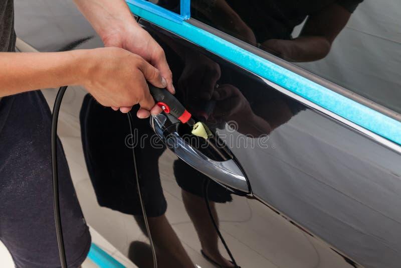 Ο στιλβωτής γυαλίζει το σώμα του οχήματος με το ειδικό κερί για να προστατεύσει το αυτοκίνητο από τις δευτερεύουσες αρχές και τη  στοκ εικόνες με δικαίωμα ελεύθερης χρήσης