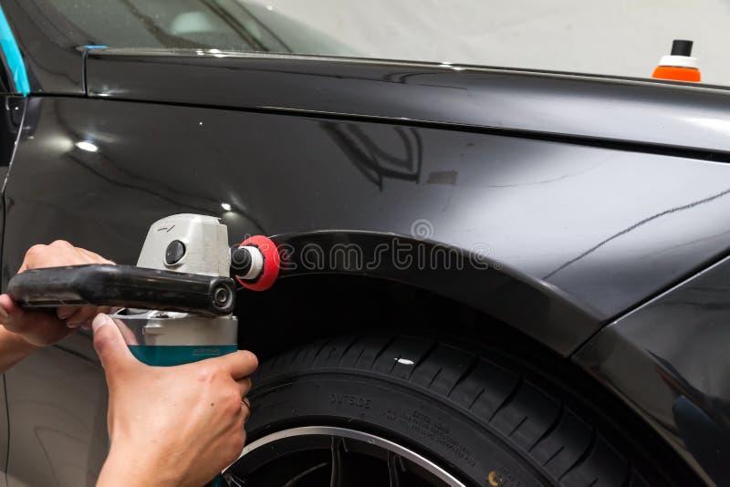 Ο στιλβωτής γυαλίζει το σώμα του οχήματος με το ειδικό κερί για να προστατεύσει το αυτοκίνητο από τις δευτερεύουσες αρχές και τη  στοκ εικόνα