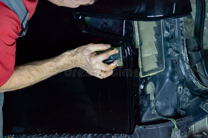 Ο στιλβωτής καλύπτει το σώμα του οχήματος με το ειδικό κερί για να προστατεύσει το αυτοκίνητο από τις δευτερεύουσες αρχές και τη  στοκ εικόνα