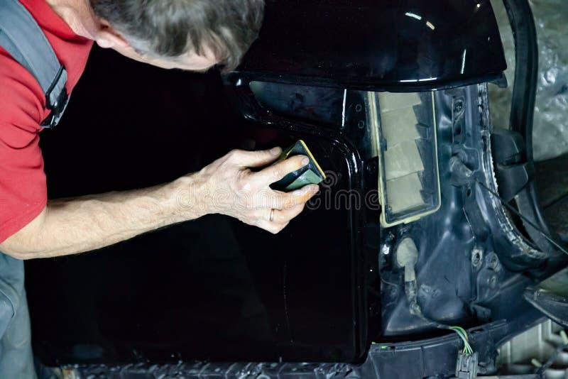 Ο στιλβωτής καλύπτει το σώμα του οχήματος με το ειδικό κερί για να προστατεύσει το αυτοκίνητο από τις δευτερεύουσες αρχές και τη  στοκ εικόνα με δικαίωμα ελεύθερης χρήσης