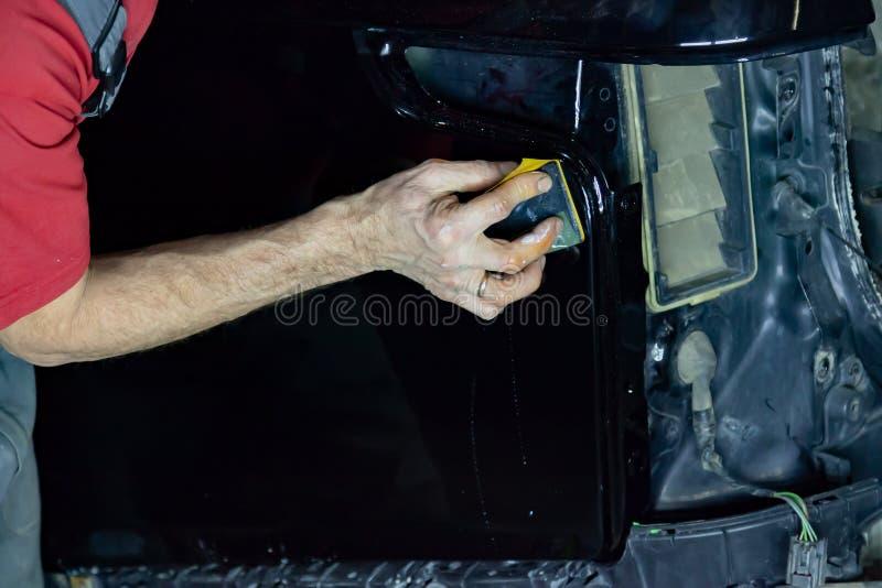 Ο στιλβωτής καλύπτει το σώμα του οχήματος με το ειδικό κερί για να προστατεύσει το αυτοκίνητο από τις δευτερεύουσες αρχές και τη  στοκ εικόνες