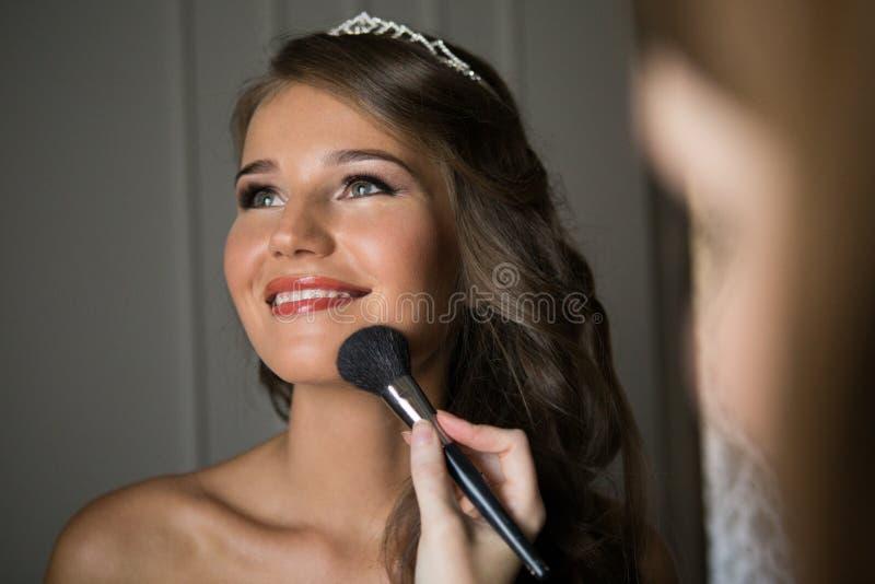 Ο στιλίστας κάνει makeup τη νύφη στη ημέρα γάμου στοκ φωτογραφία