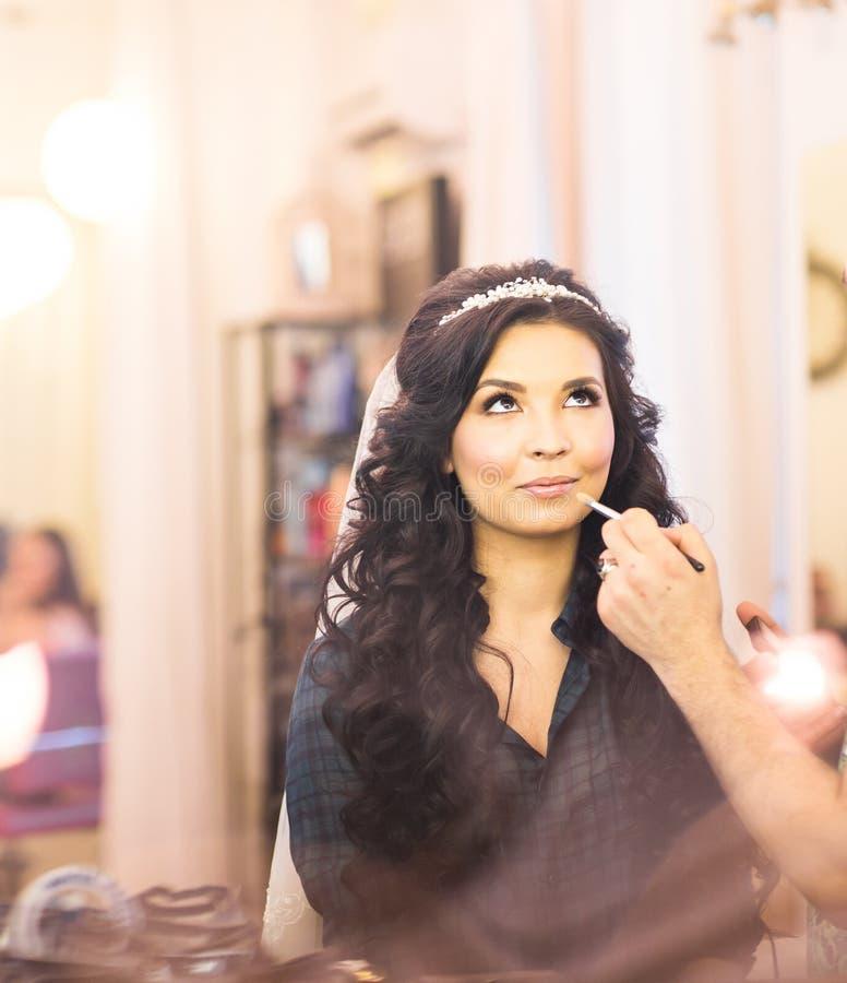 Ο στιλίστας κάνει makeup τη νύφη στη ημέρα γάμου στοκ εικόνες
