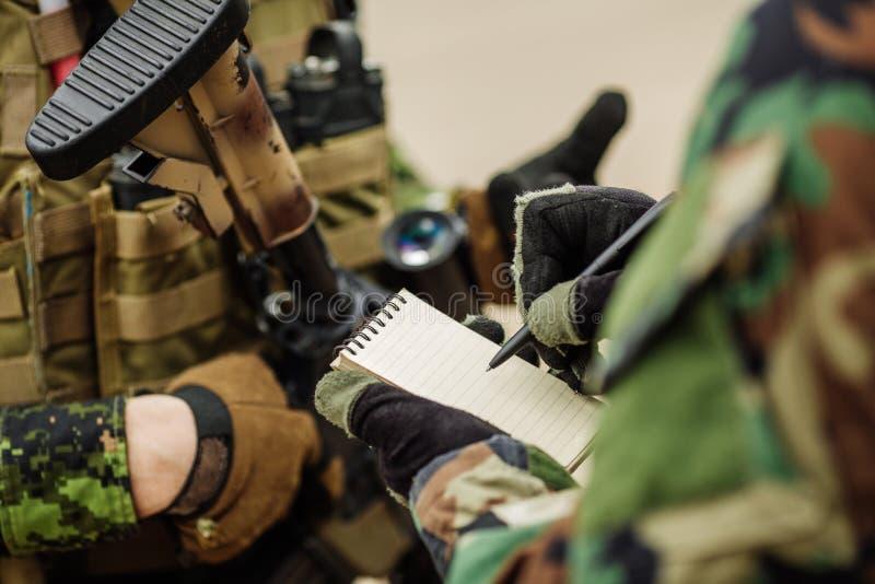 Ο στρατιώτης έγραψε τη μάνδρα σε ένα σχέδιο δράσης σημειωματάριων στοκ εικόνα