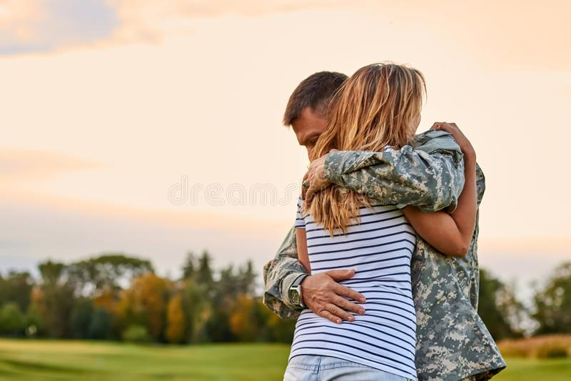 Ο στρατιώτης αγκαλιάζει μια γυναίκα υπαίθρια στοκ εικόνα