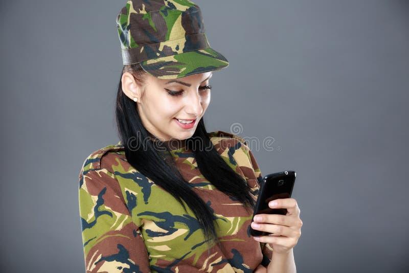 ο στρατιώτης γυναικών εξετάζει ένα κινητό τηλέφωνο στοκ φωτογραφία με δικαίωμα ελεύθερης χρήσης
