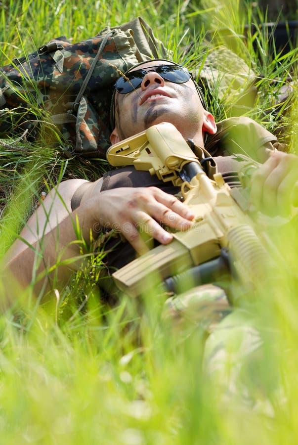 Ο στρατιώτης παίρνει ένα υπόλοιπο όταν τελειώνει η μάχη στοκ εικόνα με δικαίωμα ελεύθερης χρήσης