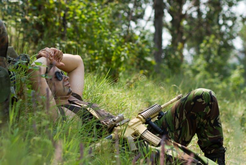 Ο στρατιώτης παίρνει το υπόλοιπο που βρίσκεται σε μια χλόη στοκ φωτογραφία με δικαίωμα ελεύθερης χρήσης