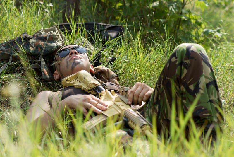Ο στρατιώτης παίρνει το υπόλοιπο που βρίσκεται σε μια χλόη στοκ εικόνα με δικαίωμα ελεύθερης χρήσης