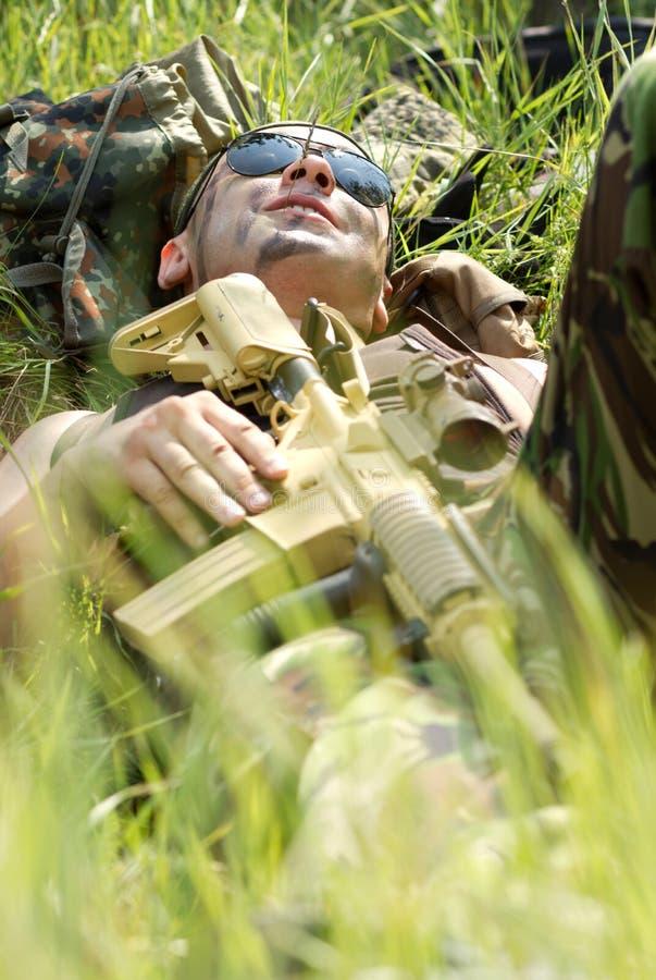 Ο στρατιώτης παίρνει το υπόλοιπο που βρίσκεται σε μια χλόη στοκ εικόνες με δικαίωμα ελεύθερης χρήσης
