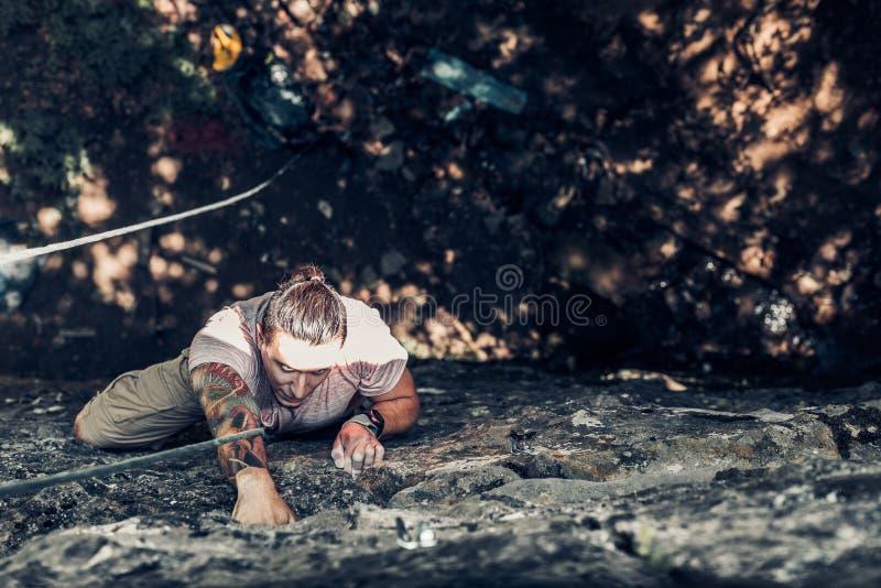 Ο συγκεντρωμένος αρσενικός ορειβάτης αναρριχείται σε έναν απότομο βράχο Ακραία έννοια δραστηριότητας τρόπου ζωής υπαίθρια στοκ φωτογραφία με δικαίωμα ελεύθερης χρήσης