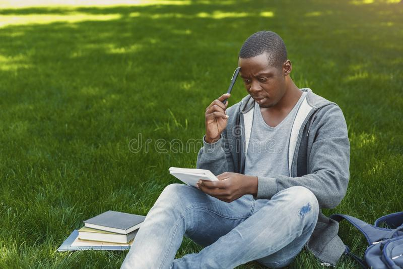 Ο συγκεντρωμένος αφροαμερικάνος η συνεδρίαση με το σημειωματάριο στη χλόη στοκ εικόνες με δικαίωμα ελεύθερης χρήσης