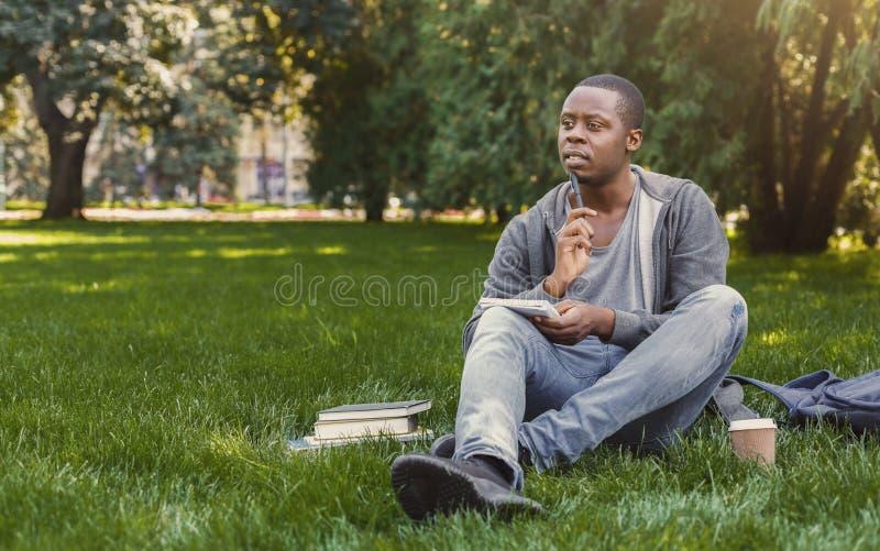 Ο συγκεντρωμένος αφροαμερικάνος η συνεδρίαση με το σημειωματάριο στη χλόη στοκ εικόνα