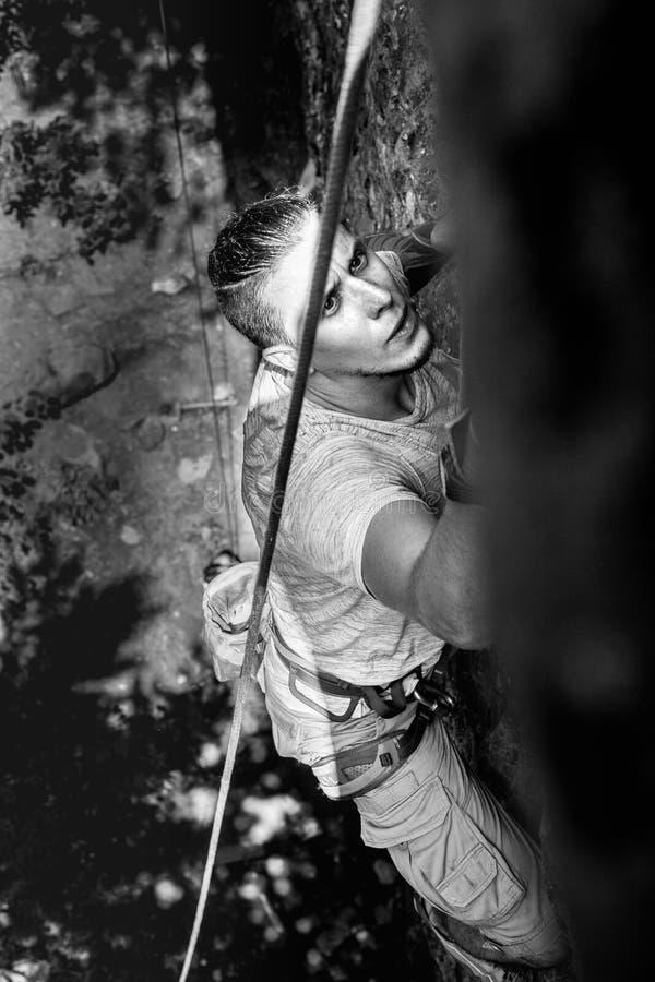 Ο συγκεντρωμένος ορειβάτης αναρριχείται σε έναν απότομο απότομο βράχο Ακραία έννοια δραστηριότητας τρόπου ζωής υπαίθρια στοκ εικόνες