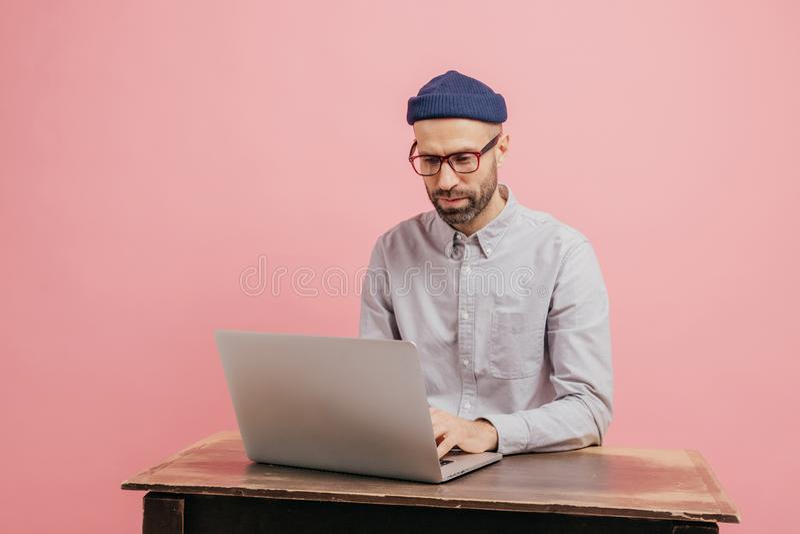 Ο συγκεντρωμένος hipster σπουδαστής διαβάζει τις πληροφορίες και ελέγχει οι στοιχείου, όργανο ελέγχου φορητός προσωπικός υπολογισ στοκ εικόνα