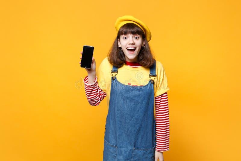 Ο συγκινημένος έφηβος κοριτσιών γαλλικό beret, κινητό τηλέφωνο εκμετάλλευσης τζιν sundress με την κενή κενή οθόνη απομόνωσε σε κί στοκ εικόνες με δικαίωμα ελεύθερης χρήσης