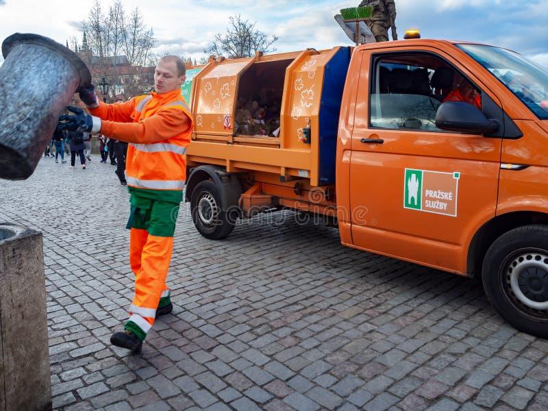 Ο συλλέκτης απορριμάτων χύνει τα απορρίματα στο φορτηγό απορριμάτων στοκ εικόνες