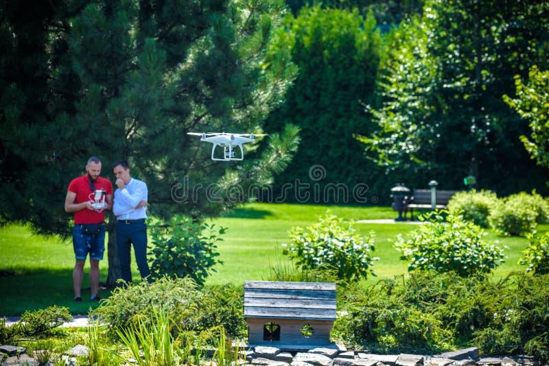 Ο συμπαγής κηφήνας αιωρείται μπροστά από δύο άτομα hipster Το τετράγωνο copter πετά κοντά σε πειραματικό Farmer και γεωπόνος που  στοκ φωτογραφίες με δικαίωμα ελεύθερης χρήσης