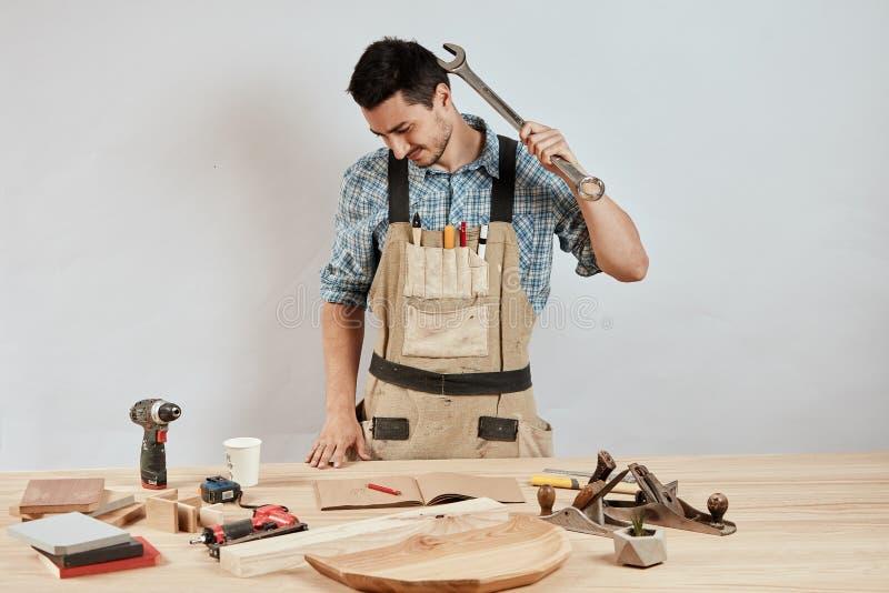 Ο συναισθηματικός αρσενικός ξυλουργός σε workwear και η ποδιά που έχει συγχύσει μπερδεμένος κοιτάζουν στοκ φωτογραφία με δικαίωμα ελεύθερης χρήσης