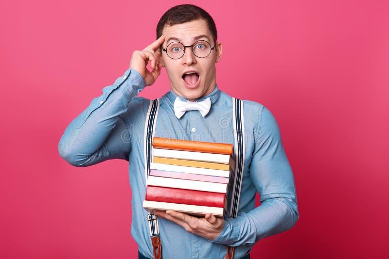 Ο συναισθηματικός δημιουργικός μελαχροινός μαλλιαρός νεαρός άνδρας βάζει το δείκτη στο ναό του, κρατά πολλά βιβλία σε ένα χέρι, α στοκ φωτογραφία με δικαίωμα ελεύθερης χρήσης