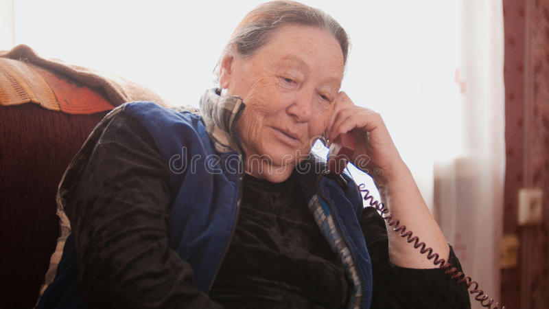 Ο συνταξιούχος ηλικιωμένων γυναικών μιλά το τηλέφωνο γραμμών εδάφους και χαμογελώντας, κλείστε επάνω στοκ φωτογραφίες με δικαίωμα ελεύθερης χρήσης