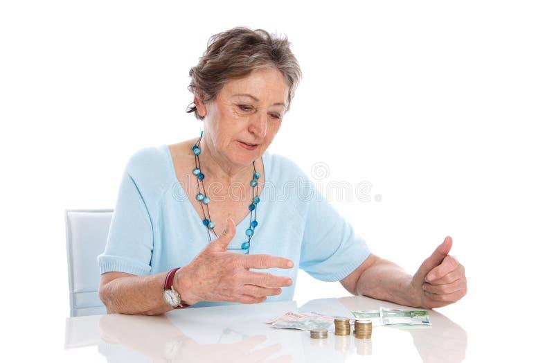 Ο συνταξιούχος μετρά το εισόδημά της - ηλικιωμένη γυναίκα που απομονώνεται στην άσπρη πλάτη στοκ φωτογραφία