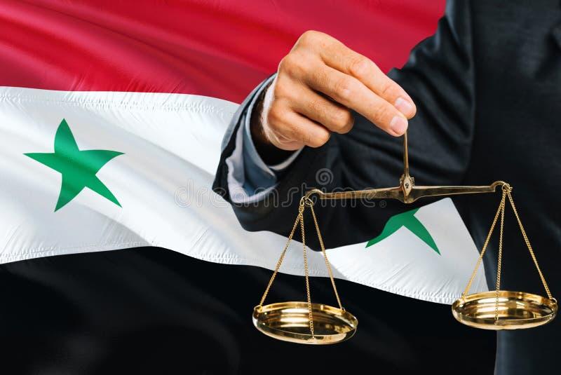 Ο συριακός δικαστής κρατά τις χρυσές κλίμακες της δικαιοσύνης με το κυματίζοντας υπόβαθρο σημαιών της Συρίας Θέμα ισότητας και νο στοκ φωτογραφίες