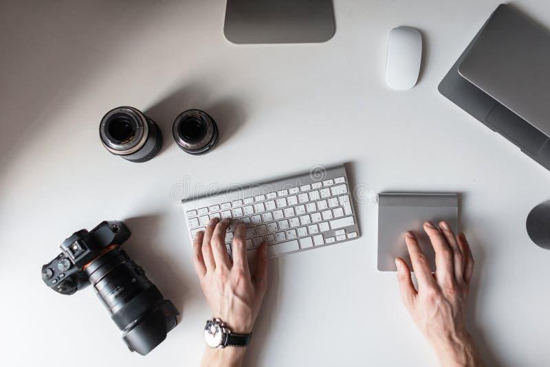 Ο σχεδιαστής κάθεται στον εργασιακό χώρο και δακτυλογραφεί στο πληκτρολόγιο Τοπ άποψη των χεριών των ατόμων και σχετικά με έναν π στοκ εικόνες