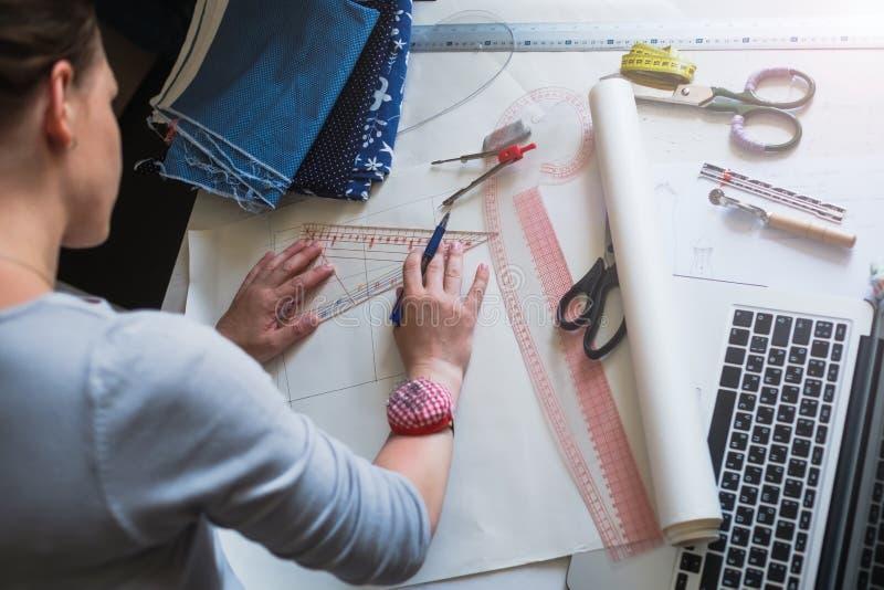 Ο σχεδιαστής μόδας σύρει το σχέδιο για τα ενδύματα στοκ εικόνες