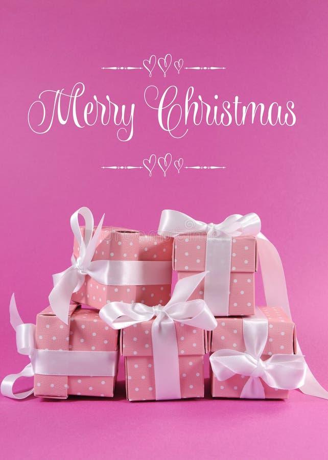 Ο σωρός του όμορφου ρόδινου δώρου σημείων Πόλκα παρουσιάζει με το χαιρετισμό Χαρούμενα Χριστούγεννας στοκ φωτογραφία