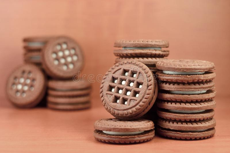 Ο σωρός των μπισκότων τσιπ σοκολάτας που γεμίζουν με την άσπρη κρέμα βανίλιας βρίσκεται στην ξύλινη καφετιά επιφάνεια Γλυκό και ν στοκ εικόνες με δικαίωμα ελεύθερης χρήσης
