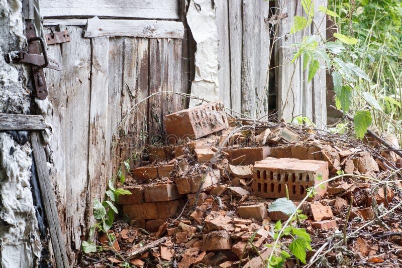 Ο σωρός των παλαιών ραγισμένων κόκκινων τούβλων δίπλωσε κοντά στο ξύλινο υπόστεγο στοκ φωτογραφία με δικαίωμα ελεύθερης χρήσης