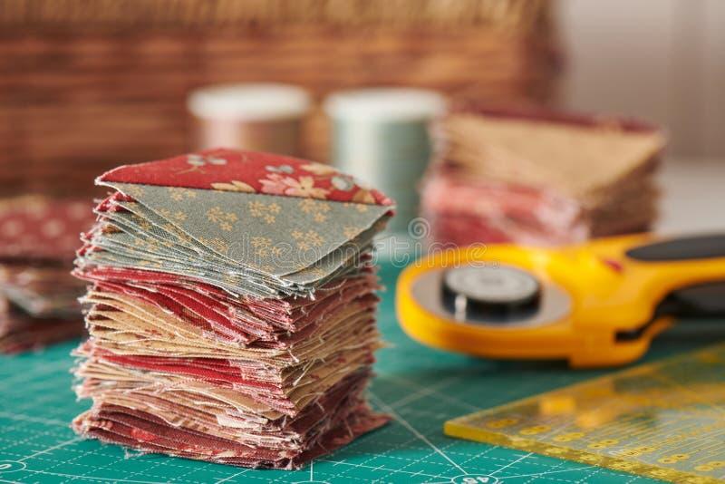 Ο σωρός των τετραγωνικών κομματιών έραψε από τις φέτες τριγώνων στο χαλί carft, που ράβει τα εξαρτήματα στοκ φωτογραφία με δικαίωμα ελεύθερης χρήσης