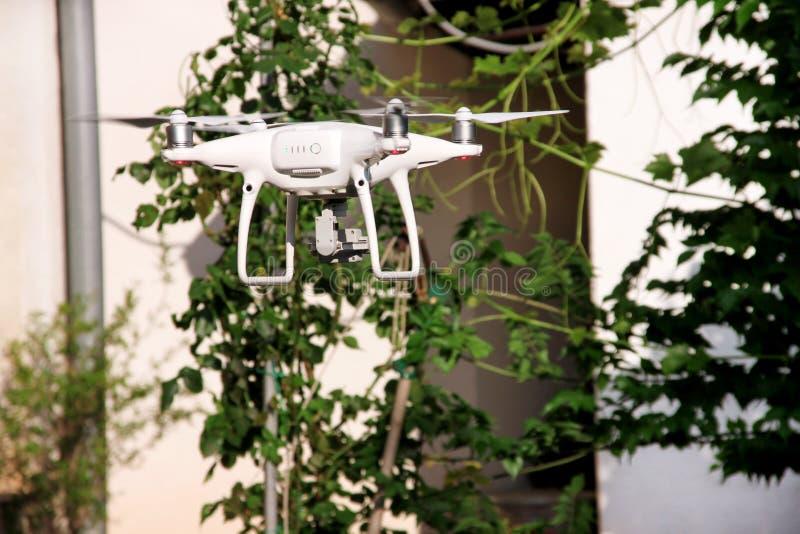 Ο σύγχρονος άσπρος κηφήνας τετραγώνων copter με 4K τη ψηφιακή κάμερα πετά στον αέρα, για να πάρει τις φωτογραφίες και να καταγράψ στοκ εικόνα