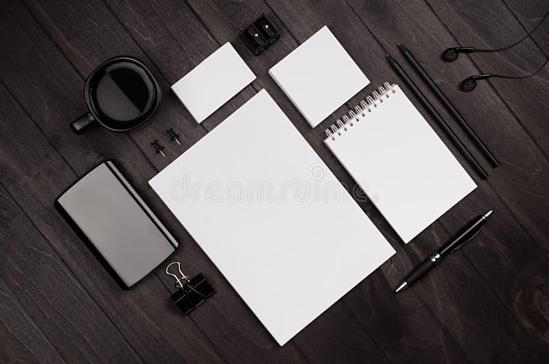 Ο σύγχρονος minimalistic χώρος εργασίας με τα κενά χαρτικά στο μαύρο ξύλινο πίνακα, τοπ άποψη, έκλινε στοκ εικόνα