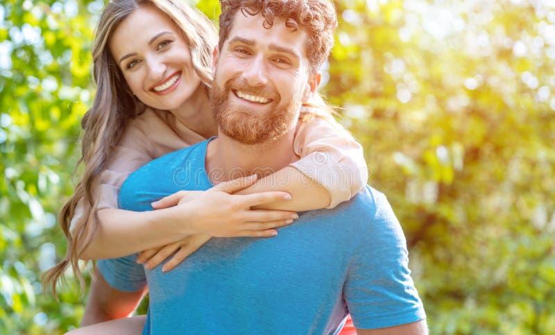 Ο σύζυγος φέρνει τη σύζυγό του στην πλάτη του που είναι αξιόπιστος συνεργάτης στοκ φωτογραφίες με δικαίωμα ελεύθερης χρήσης