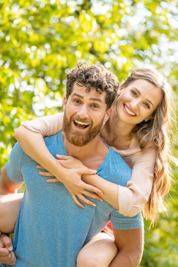 Ο σύζυγος φέρνει τη σύζυγό του στην πλάτη του που είναι αξιόπιστος συνεργάτης στοκ φωτογραφία με δικαίωμα ελεύθερης χρήσης