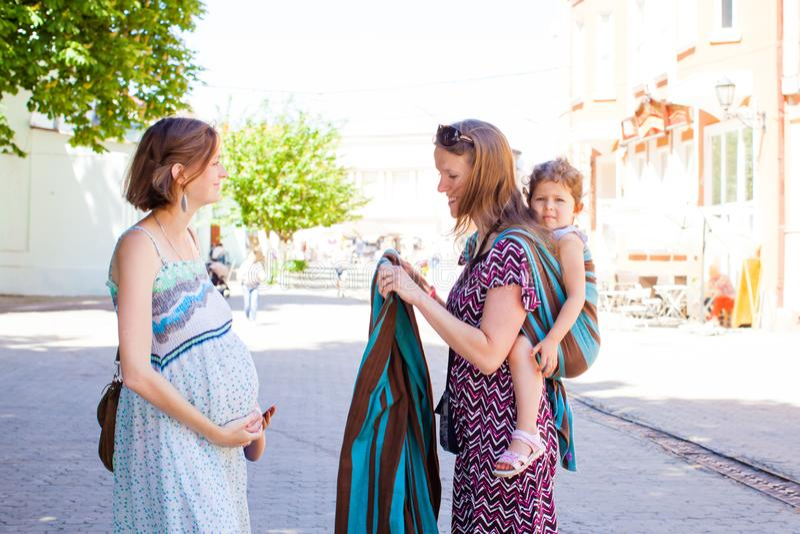 Ο σύμβουλος Babywearing συναντά την έγκυο κυρία υπαίθρια στο πάρκο στοκ εικόνες