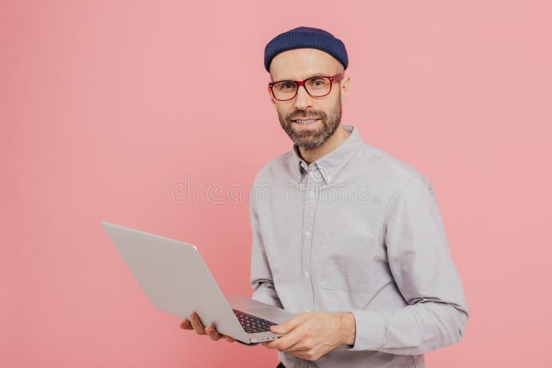 Ο ταλαντούχος αρσενικός δημοσιογράφος με να απευθυνθεί κοιτάζει, κρατά το σύγχρονο φορητό προσωπικό υπολογιστή, εργάζεται στο νέο στοκ φωτογραφία