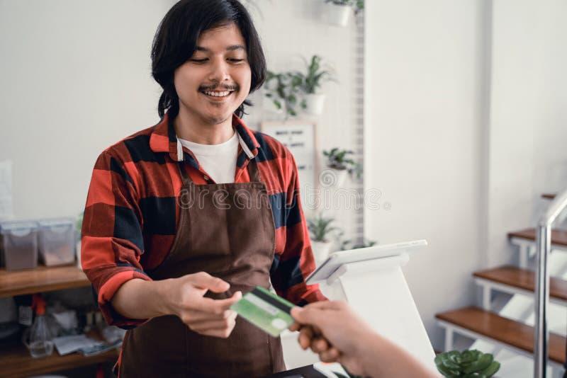 Ο ταμίας στον καφέ δέχεται τις πληρωμές με πιστωτική κάρτα στοκ εικόνα